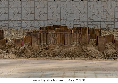 Steel Girder Beams Protruding Above Ground In Front Of Concrete Wall At Construction Site.