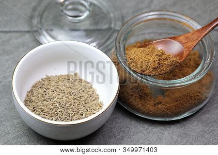 An Indian Spice Powder Which Is Made Of Roasted Cumin Seeds In A Jar On Grey Background.