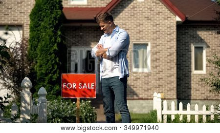 Happy House Owner Looking At For Sale Signboard Against House, Moving Concept