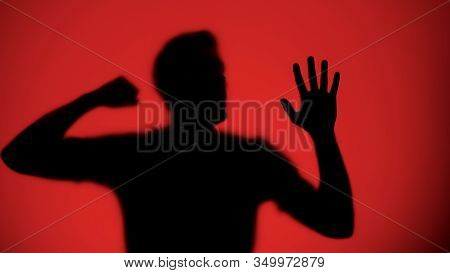 Male Silhouette Knocking On Glass, Red Light Background, Warfare Concept