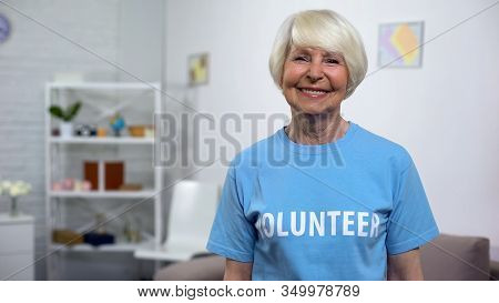 Smiling Senior Lady In Volunteer T-shirt Looking Camera, Charity Organization