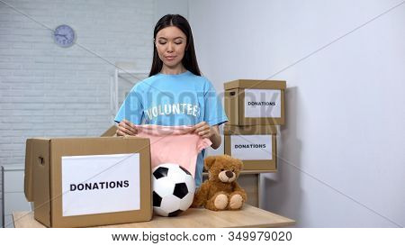 Social Worker Putting Clothes And Toys In Box, Helping Orphans, Donation