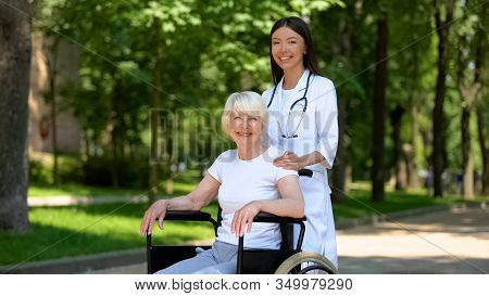 Female Nurse And Disabled Aged Woman Smiling To Camera, Relax In Hospital Park