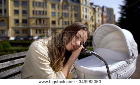 Exhausted Mother Sleeping On Newborn Carriage Sitting On Bench, Exhaustion
