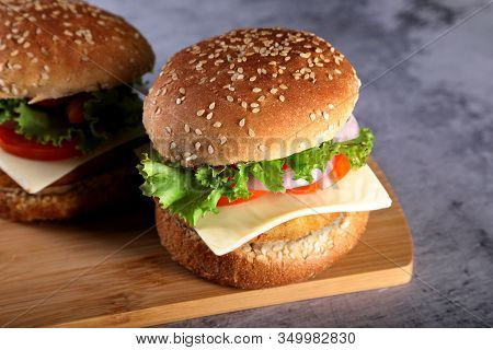 Fast Food - Burgers On A Wooden Mat With Textured Background