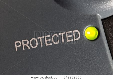 Macro close up photograph of protected indicator light on electric surge protection device.