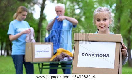 Smiling Girl Holding Donation Box, Volunteers Preparing Humanitarian Aid, Help