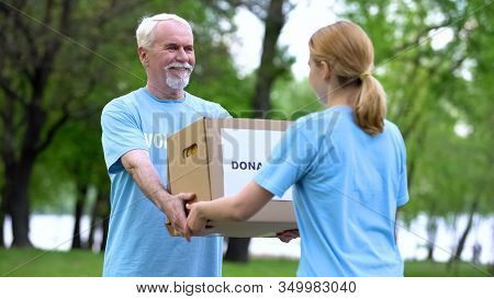 Happy Aged Volunteer Giving Donation Box Young Woman, Humanitarian Aid, Charity