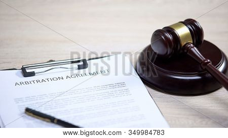 Arbitration Agreement Document On Table, Gavel Lying On Sound Block, Dispute