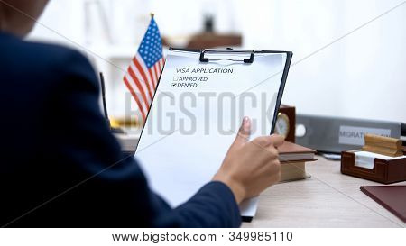 Female Immigration Inspector Denying Visa Application, American Flag On Table