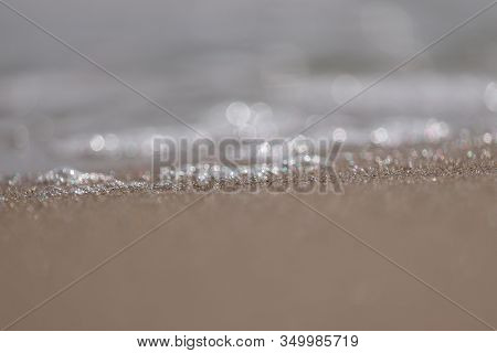 Close Up Sharp Shot Of Sea Water Wave On Beach With Selective Focus Background And Sandy Foreground,