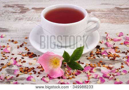 Cup Of Hot Tea With Wild Rose, Fresh Blooming Flowers And Dried Petals With Tea Grains On Old Wooden