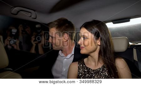 Smiling Star Couple Looking At Paparazzi From Car, Enjoying Fame And Glory