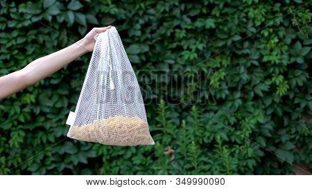 Hand Demonstrating Pasta In Reusable Crochet Bag, Reducing Polypropylene Usage
