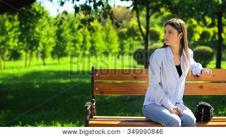 Young Female Waiting In Park Sitting On Bench, Appointment Punctuality, Time
