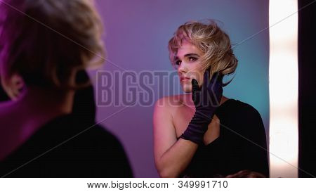Travesty Diva In Dress And Blond Wig Looking In Mirror Before Performance, Show