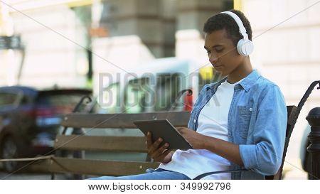 Serious Black Male Teenager In Headphones Working On Tablet Outdoors, Freelance