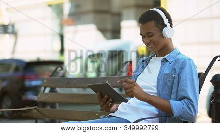 Cheerful Mixed-race Boy In Headphones Using Tablet Outdoors, Listening To Music
