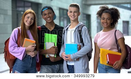 Multiracial High School Students With Books Smiling Camera, Educational Program