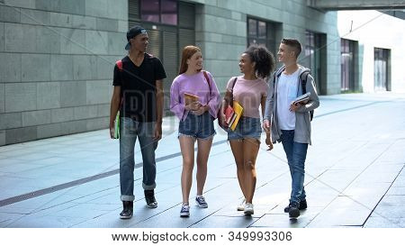 Multiethnic Teenagers With Books Walking Campus During Lessons Break, College