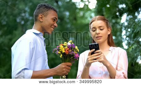 Indifferent Teen Girl Ignoring Boyfriend Presenting Flowers, Chatting Smartphone