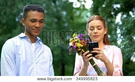 Gadget Addicted Girl With Flowers Chatting On Smartphone Ignoring Boyfriend