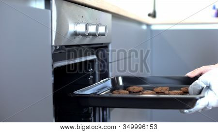 Woman Putting Chocolate Cookies In Oven, Recipes Of Homemade Baking, Confection