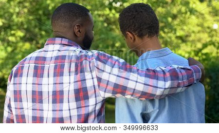 Afro-american Father Hugging Son Outdoors Smiling Each Other, Family Connection