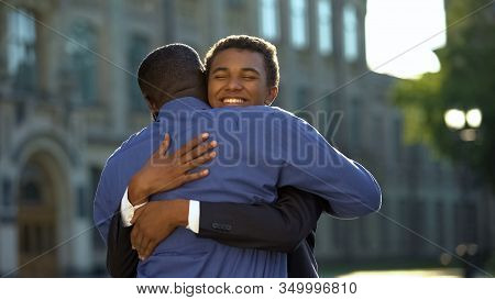 Glad Parent Hugging Young Son In Suit Outdoors University, Prom Celebration