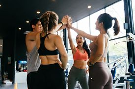Smile Man And Women Making Hands Together In Fitness Gym. Group Of Young People Doing High Five Gest