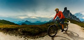 Single mountain bike rider on electric bike, e-mountainbike rides up mountain trail. Man riding on bike in Dolomites mountains landscape. Cycling e-mtb enduro trail track. Outdoor sport activity.