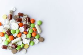 Medicines And Pills. Multicolored Medicines On A White Background Close-up. A Slide Of Colored Table