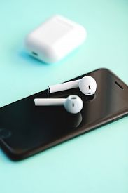 Smartphone And Wireless Earphones Isolated On The Blue Background.
