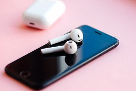 Smartphone And Wireless Earphones Isolated On The Pink Background.