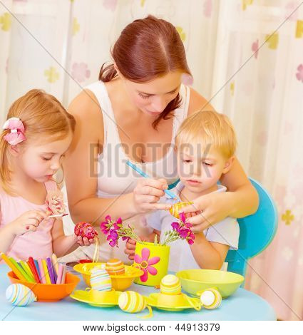 Two small cute children with beautiful mother paint Easter eggs at home, mom teaching babies decorate traditional eastertime symbol