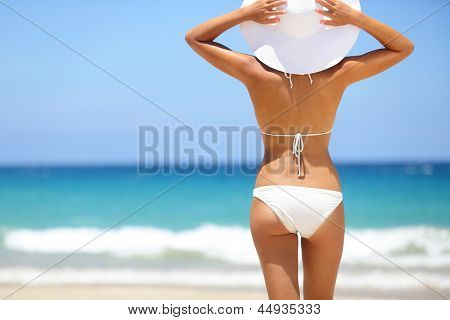 Beach vacation. Hot beautiful woman in sunhat and bikini standing with her arms raised to her head enjoying looking view of beach ocean on hot summer day. Photo from Hapuna beach, Big Island, Hawaii.