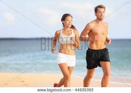 Couple running. Sport runners jogging on beach working out smiling happy. Fit male fitness model and attractive female jogger. Multiracial group, Asian woman and Caucasian man.