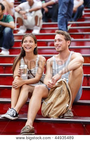 Dating multiracial tourist couple in New York City, Manhattan on the red stairs and steps on Times Square. Happy multiethnic young couple on date enjoying coffee. Asian woman, white Caucasian man.