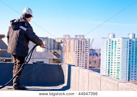 Roofer worker installing roofing felt by means of gas blowpipe torch poster