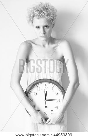 Scrawny girl with big clock in hands, black and white photo.