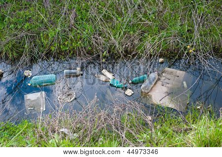 Concept or conceptual unhygienic polluted river,sewage or dirty water and grass with waste,trash and dump background poster