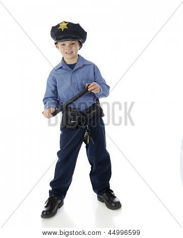 Full length image of a young elementary boy happily standing in his police uniform with his nightstick in hand.  On a white background.