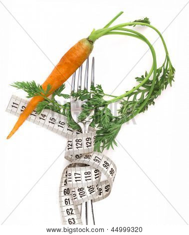fresh carrot with leaves on the fork with measuring tape, diet concept