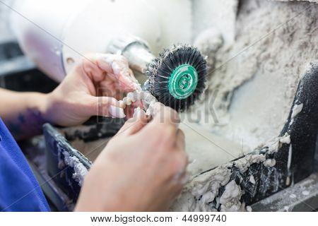 Dental Technician Polishing A Prosthesis