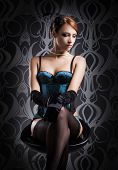 Beautiful and sexy cabaret artist in lingerie over vintage background poster