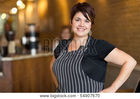 Portrait of happy young female owner with hands on hips standing in coffee shop