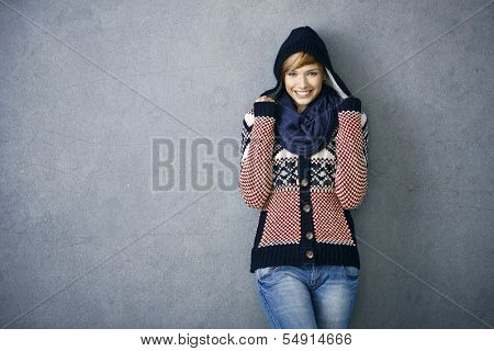 Attractive young woman wearing warm nordic sweater and hat, smiling