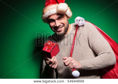 santa man is dissapointed about the size of his present, on green background