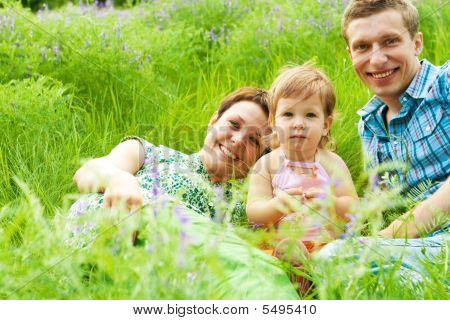 Family Having Rest In Grass
