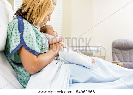 Mid adult woman looking at newborn babygirl while sitting on hospital bed